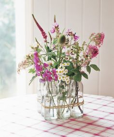 Create a simple yet elegant centerpiece by using a bunch of vintage milk bottles to hold flowers aloft. Simply line up nine same-size vessels in three rows of three. Then wrap gardener's twine around the grouping twice and tie the ends. Finish the blooming display by placing two to three stems in each container. Smart idea: Separate the milk bottles and flowers afterwards to give to your guests as party favors. - CountryLiving.com