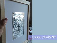 Im Gegenlicht schimmert die Prägefolie silbern und die geprägten Linien werfen deutliche Schatten. Das Passepartout und das Relief liegen nicht - wie üblich - hinter dem schützenden Glas, sondern davor.