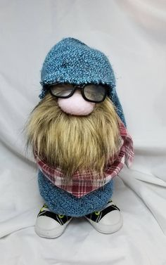 Hipster has never been so adorable!! Gudbrande stands 11 inches tall and is made with all new material including a polyester blend knit fabric, flannel wrap, fleece, faux fur, plastic glasses, canvas and vinyl sneakers, polyester fiberfill, rice for a weighted base and of course, love!