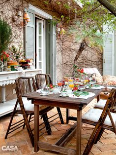 O quintal é equipado com mesa de refeições (Leroy Merlin) e um nicho secreto, fechado com uma porta veneziana verde que oculta churrasqueira e forno de pizza. Cadeiras e aparador da Entreposto.