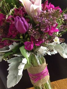 Spring bouquet of lilac, freesia, tulips, waxflower and dusty miller.