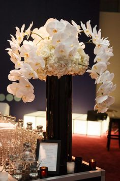A cloud of white hydrangeas and branches of orchids contrast with a black cylindrical vase.
