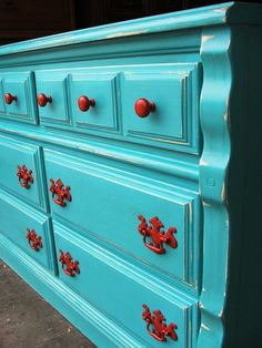 Lightly distressed pretty blue dresser.  Like the pop of red on the hardware!