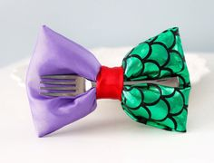 This amazing hair bow is perfect for all girls who love Disney Princesses! Inspired by Disneys The Little Mermaid Ariel. Created this amazing design for Disney trips,birthday parties or just an ordinary day!  A fork embellishment adds to the finishing touch!  This bow measures approximately 4 - 5 It comes attached to an Alligator Clip or French Barrette.  Also you can choose from two different styles.  >Pillow Bow >Classic Bow  **The model girl is wearing a pillow bow. Small parts may pose a…