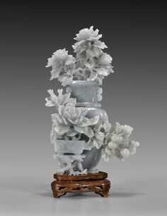 """Fine Chinese carved pale jadeite covered urn; the flattened form with a stand holding flower pot issuing forth large openwork blossoms of roses and chrysanthemums; the cover with tall branching peonies; the stone of translucent pale green; H: 9 1/4""""; wire inlaid wood stand Jade Crystal, Cool Rocks, Chrysanthemums, China Art, Minerals And Gemstones, Stone Carving, Traditional Art, Buddhism, Stone Jewelry"""