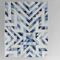 Blue and white patchwork quilt with star motif hanging in front of a white wall