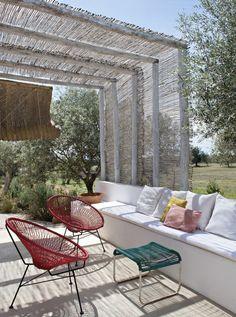 Un espace farniente ombragé. Plafond traditionnel en canisses chaulées. Fauteuils rouges des années 60, chaises en fil de plastique Henkel Ideal et banquette en béton blanchi