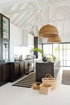 Coastal kitchen with large wicker pendant lights and dark cabinets with white walls