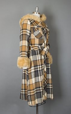 ♡ PLEASE ENLARGE PHOTOS FOR MORE DETAIL ♡  • 1970s princess coat • plaid • acrylic • tan, grey, + cream • large hood • plush faux shearling cuffs + trim on hood • two breast pockets + two in-seam hip pockets • button closures • fitted waist with attached side ties • a-line skirt • lined in acetate  D E T A I L S label: none present, not handmade content: acrylic fits like a: small | medium  M E A S U R E M E N T S shoulders: 15.5 bust (doubled): 38 waist (doubled): up to 33 hips (doubled)…