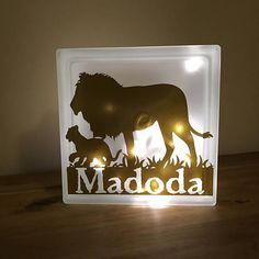 Masterful Lion with Cub walking across an LED fairy lights Night Light, Vinyl Design Overlaid Glass Block, creating twinkles of illuminated magic.  These blocks are perfect as an occasional light, as a nightlight for your home, or a gift for friends or family. Lovingly handmade to order in Worksop, Nottinghamshire and shipped across the entire UK.