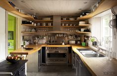 Designed by Gert Wingardh, this Swedish kitchen's custom countertops and shelving are birch, the oven and cooktop are by Gaggenau, and the antique stove in the foreground is original to the house. Tour the entire home. Jean-Francois Jaussaud/Luxproductions  - ELLEDecor.com