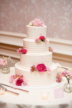 Romantic shades of pink and red flowers with ivory, round, layered cake is fantastic! Photo credit: Annie Hosfeld Photography http://www.chestercountyweddingflowers.com