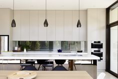 low window for the kitchen with overhead cupboards, pendant lights by Edward Linacre