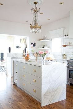 a modern glam kitchen with a tall hanging chandlier with brass details and sheer crystals
