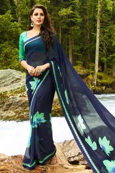 Grab the attention of your onlookers by cladding in this navy color vibrant printed party wear georgette fabric saree adorned elegantly with fancy print and lace work which is the main highlight of the saree This saree is an apt choice of outfit for casual parties and social events when paired with simple fashionable jewellery The saree comes along with matching fabric unstitched blouse piece that can be custom made upto the bust size of 42 inches