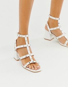 24 Wedding Sandals You Can Definitely Wear Again - close-up of a models feet wearing strappy white sandals decorated with silver studs - Public Desire white studded mid heeled sandals, $42, ASOS