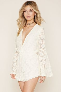 A romper crafted from knit floral lace with long bell sleeves, a plunging V-neckline, an elasticized waist, and scalloped trim.