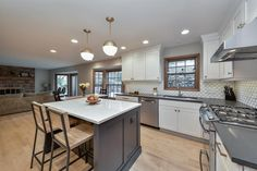 Adjacent to the living room, this spacious, open plan kitchen boasts a stylish, updated look with a beautiful gray and white color scheme. A pair of light wood barstools that match the floors offer seating at the island.
