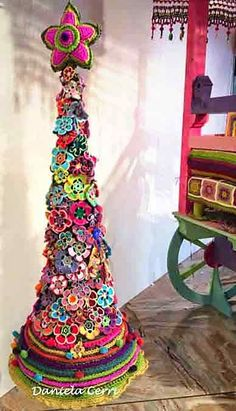 Crochet flower Christmas tree. I plan to put a base of green flowers and top them with colorful flowers. Great and very cute idea.