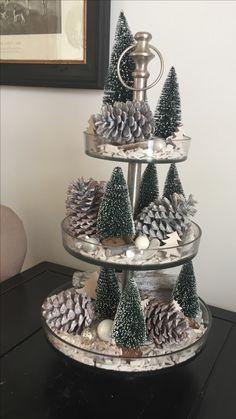 Etagère Rivièra Maison Opgemaakt met witte houtsnippers, mini kerstboompjes (Action) en wit gespoten dennenappels. Daarnaast boomschors en een paar kerstballen. Christmas Kerst Kerstmis