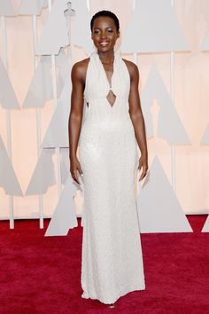 Lupita Nyong'o hits the Oscars red carpet in a custom gown by Calvin Klein, constructed entirely of pearls. See the best red carpet arrivals, here: