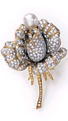 A DIAMOND AND BAROQUE CULTURED PEARL BROOCH Designed as a pavé-set diamond rose, enhanced by a baroque cultured pearl, measuring approximately 12.60 mm, mounted in gold and platinum, (with interchangeable pear-shaped diamond accent, weighing approximately 2.37 carats