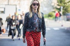 A floral jacket is paired with a gray top, printed pants, and square sunglasses