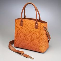 Rich ostrich embossing distinguishes this refined leather tote. Designed with an organized interior and plenty of pockets, this tote is sure to fit your daily needs. This spacious tote has rolled hand