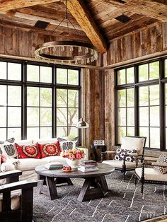 Large grid windows bring natural light into the living room, while bright throw pillows add a pop of color to the otherwise neutral scheme. Wood paneling on the walls adds a rustic, cabinlike feel to the room, while an oversize chandelier adds an element of sophistication./