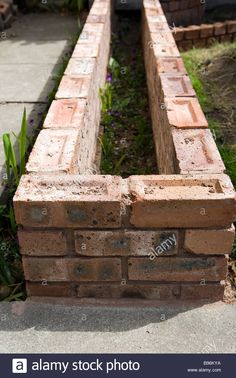 Small brick wall that is to be used as a raised bed in a garden Stock Photo