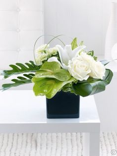 Featuring 2 aspidistra leaves, 3 white large-headed roses, 2 philodendron xanadu, white oriental lilies, 2 green anthurium and 3 green carnations with steel grass and pittosporum, presented in a black cube vase by Flowers.ie. Order Flowers Ireland