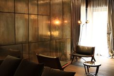 Parallel House - interior by privatiselectionem.com; View to  the day activity living area. Polished silvered brass wall panneling reflects the DC90 armchairs  designed by Vincenzo De Cotiis for Ceccotti Collezioni.
