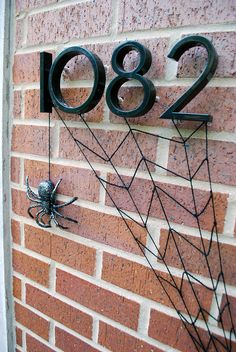 DIY #spookyspaces #Halloween front door decoration - Yarn spiderweb and glitter-painted spider hanging from address numbers