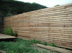 """brilliant and cheap idea of purchasing 8-foot sections of cedar picket fencing from [shudder] Home Depot, cutting off the tips, and turning them on their sides."""