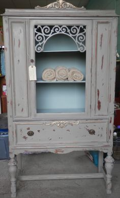 "This was an antique depression era china cabinet and I painted it with ""Annie Sloan"" chalk paint in French Linen on the outside and Duck Egg Blue on the inside, buffed with a clear wax and added AS gilding wax in Empire Gold on the top and on the drawer.LP"