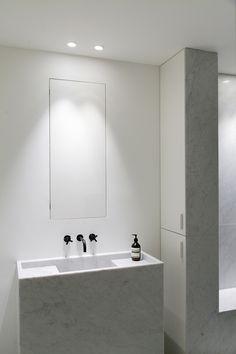 Carrara marble sink + hidden mirror (cabinet) + bold black Hansgrohe tap. Minimal bathroom by Annemarie van Riet.