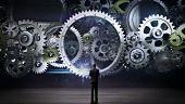 Medium Businessman standing big Gear wheels, connecting gear wheels.