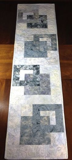 Although designed as a modern look table runner, this quilt could also be used to adorn your wall, a dresser, coffee table, sofa table, buffet, desk, bed or piano top. The gray color scheme is versatile and can be used in any season. A layer of batting enclosed between two layers of cotton