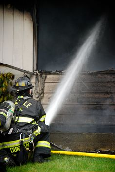 A fireman shoots water up toward a ceiling to douse any hotspots in a residential fire. Photo by Patrick Robinson