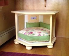 """Brighten up a hexagon-shaped dark wood end table with a fresh coat of paint and spruce up the inside to suggest a cute country doggie cottage, complete with a """"Home Sweet Home"""" sign. Fabric panels in a feminine print are Mod-Podged to the inside """"walls"""" a Cute Dog Beds, Diy Dog Bed, Pet Beds, Cute Dogs, Doggie Beds, Cheap Dog Beds, Diy Bett, Bed Parts, Dog Furniture"""