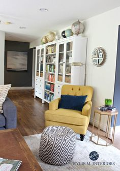 Ikea Hemnes bookcases in family room with chartreuse accent chair. Sherwin Williams Creamy paint color and home decor. Vintage, Globe collection. Kylie M Interiors E-design