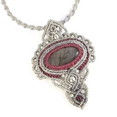 New for fall, this macrame pendant necklace features a gray flash labradorite cabochon framed in decorative macrame knotting in light gray and red. The pendant and necklace are accented with silver beads and silver seed beads. The necklace features a macrame sliding knot closure, allowing