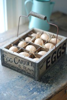 the wooden egg crate features a vintage style company logo, wire handle, and one dozen plastic eggs nestled in straw