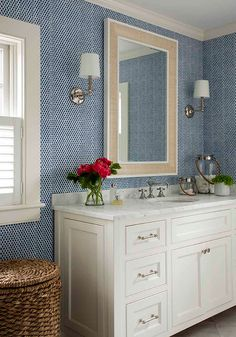 Beautifully styled white and blue bathroom features a white washstand fitted with satin nickel pulls and a white marble countertop finished with an oval sink positioned beneath a tan raffia vanity mirror flanked by polished nickel sconces mounted on blue textured wallpapered walls framing a window covered in white cafe plantation shutters positioned over a woven seagrass hamper.
