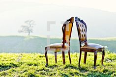 Two antique chairs in a grassy field  facing away from each other on a hillside
