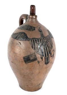 New Haven, Connecticut incised stoneware jug, ca. 1825-1830, by Absalom Stedman, with incised cobalt decorated spread winged American eagle with shield breast holding an American flag in one talon and arrows in the other. Realized Price: $402900 (world record for stoneware)