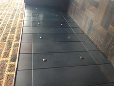Blackened steel wall cladding and buttons