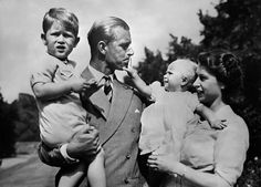 The young family.  Princess Elizabeth and Prince Philip with their 2 eldest children, Prince Charles and Princess Anne, who seems quite fascinated with her dad.