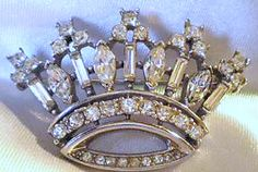 In 1941 Trifari introduced their signature crown pin. It was vermeil with colored rhinestones, cabochons and square baguette stones. It is perhaps the most identifiable, and the most copied, Vintage Trifari Jewelry design. No vintage jewelry collection is complete without one!