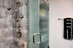 Walk-in shower with multiple shower heads and frosted glass doors in a condo with an industrial style and a contemporary feel.